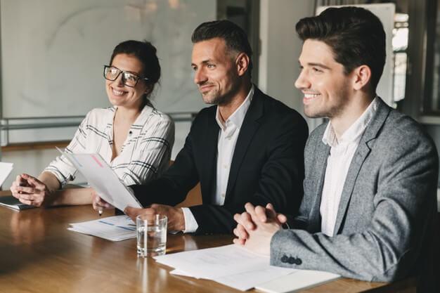 captar investidores tres pessoas sorrindo vestidas formalmente sentadas emuma mesa com papeis