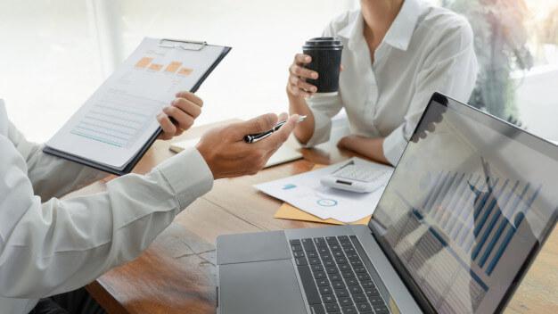 indicadores imobiliadrios duas pessoas conversando com papel na mão e notebook