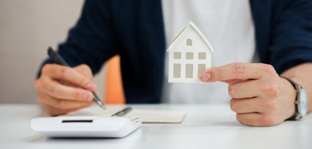 indicadores imobiliadrios homem segurando uma mini casa e usando calculadora