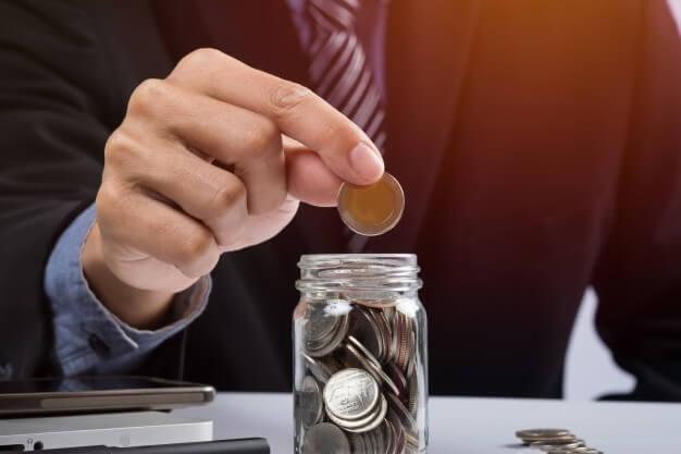 simulador de investimento homem de terno colocando moedas no pote